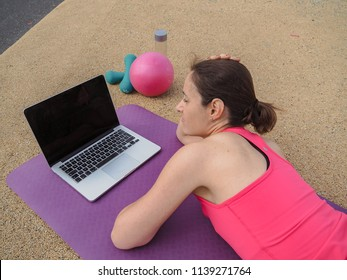 groggy woman sleeping infront of a laptop on a yoga mat after  doing a fitness workout from bird view