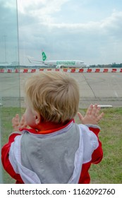 GRONINGEN AIRPORT EELDE, NETHERLANDS, AUGUST 15, 2018- Little boy looking at the Transavia Boeing 737-800 at Groningen Airport Eelde, Netherlands
