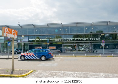 GRONINGEN AIRPORT EELDE, NETHERLANDS, AUGUST 15, 2018: The main entrance of Groningen Airport Eelde, departing and arriving travelers with a Royal Dutch Marechaussee car in front of it