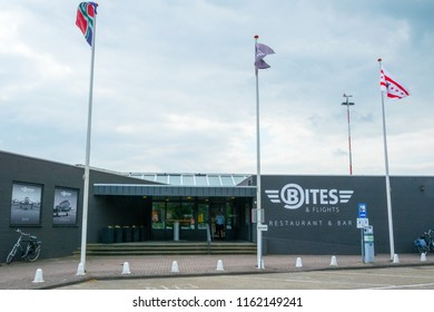 GRONINGEN AIRPORT EELDE, NETHERLANDS, AUGUST 15, 2018: Exterior of restaurant & bar, Bites and flights with three flags in front of it, at Groningen Airport Eelde, Netherlands
