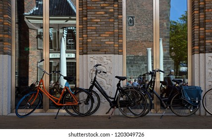 groningen, groningen/netherlands  - october 12, 2018:  bicycles parked in front of glass doors reflecting the facade of historic martini church ( martinikerk ) and cafe de kostery