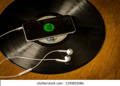 Groningen, Holland. September 29, 2018: Mobile phone with Spotify Music service in the screen and white earphones on a black vinyl record.