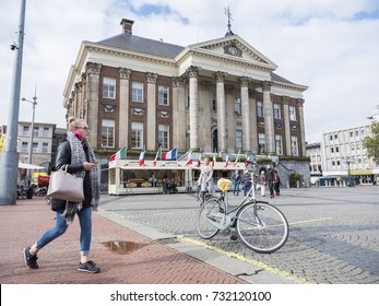 groningen, netherlands, 8 oktober 2017: young woman with mobile phone passes city hall of groningen in the netherlands