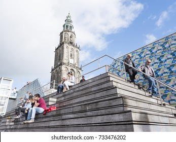 groningen, netherlands, 8 oktober 2017: people sit on steps near central square in front of martini tower in groningen on sunny day