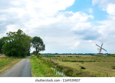 GRONINGEN, NETHERLANDS, AUGUST 15, 2018: Bike path with the White Mill (Witte Molen) on the background in Groningen, Netherlands. A typical Dutch landscape