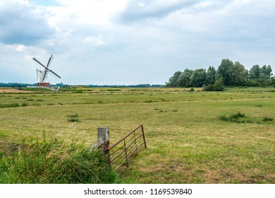 GRONINGEN, NETHERLANDS, AUGUST 15, 2018: Typical Dutch landscape with a field of grass and the White Mill (Witte Molen) in Groningen on the background