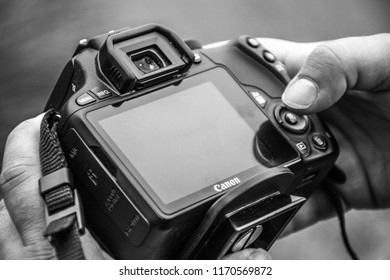 GRONINGEN, NETHERLANDS, AUGUST 19, 2018: Closeup of photographer holding a Canon eos camera, wanting to check a photo