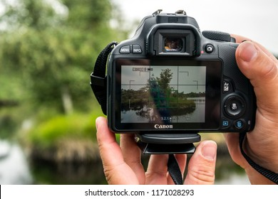 GRONINGEN, NETHERLANDS, AUGUST 19, 2018- View of a woman's hand making a photo on a Canon eos camera of a Dutch landscape
