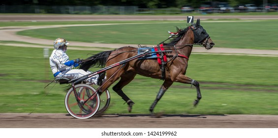 """GRONINGEN NETHERLANDS - JUNE 9, 2019: Riders compete during their harness racing or horse sulky race at the Sweepstakes Trials at """"Royal Drafbaan Groningen""""."""