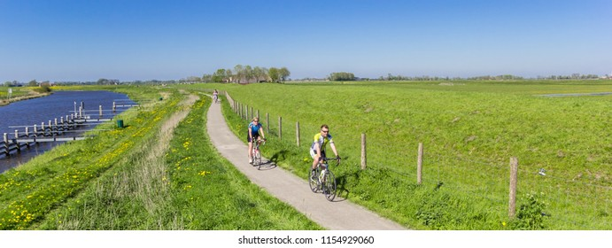 GRONINGEN, NETHERLANDS - MAY 05, 2018: Panorama of a couple riding their bicycle along the Reitdiep river in Groningen, Holland