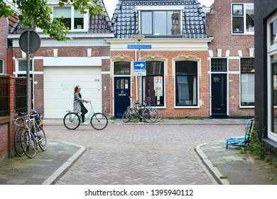 Groningen, Netherlands - May, 17, 2016: The empty street of Groningen. Street with brick houses and bicycles. A young stylish woman riding a bicycle in Netherlands.