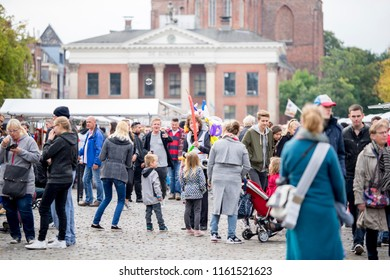 Groningen, The Netherlands - October 1, 2016: Saturday morning market in Groningen on an overcast day with in the middle of the crowd a young man selling balloon animals he makes on the spot