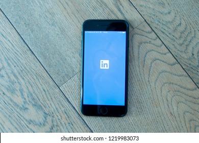 GRONINGEN, NETHERLANDS, OCTOBER 27, 2018: Close up of a black iPhone 7 with Linkedin app on a wooden background