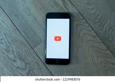 GRONINGEN, NETHERLANDS, OCTOBER 27, 2018: Close up of a black iPhone 7 with Youtube app on a wooden background