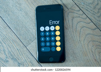 GRONINGEN, NETHERLANDS, OCTOBER 27, 2018: Close up of a black iPhone 7 with calculator app with error on a wooden background