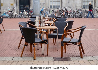 Groningen, Groningen Province, The Netherlands: 07/11/2018 European cafe tables and wicker chairs on a brick-laid city street, in the Grote Markt (Big Market), town square.
