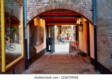 Groningen, Groningen Province / The Netherlands - 07/28/2018: Northern Shipping Museum. European medieval brick alley tunnel, with an arched entrance, leading to a shopping street.