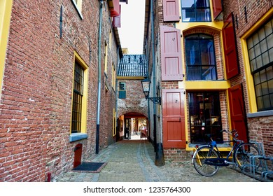 Groningen, Groningen Province / The Netherlands - 07/28/2018: Restored medieval buildings in Europe, painted with bright red and yellow trim. Traditional window hatches (shutters) & alley.