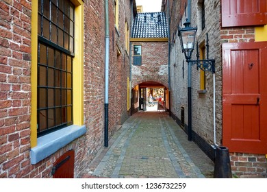 Groningen, Groningen Province / The Netherlands - 07/28/2018: Restored medieval buildings in Europe, with bright red and yellow trim. Old brick street alley with lantern and iron frame windows.
