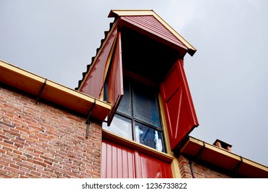 Groningen, Groningen Province / The Netherlands - 07/28/2018: Restored medieval building gable in Europe, painted with bright red hatches (window shutters) and yellow trim.