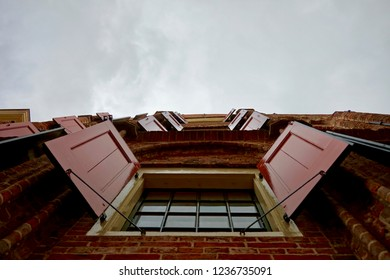 Groningen, Groningen Province / The Netherlands - 07/28/2018: Restored European medieval building window shutters (hatches), painted with bright red and yellow trim. Overcast sky.
