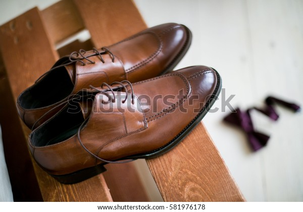 Groom Accessories: belt, wooden Butterfly, watches, cufflinks and shoes stacked in composition on a black desk