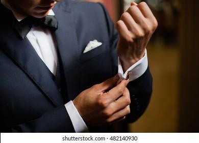 Groom is adjusting his golden cufflinks