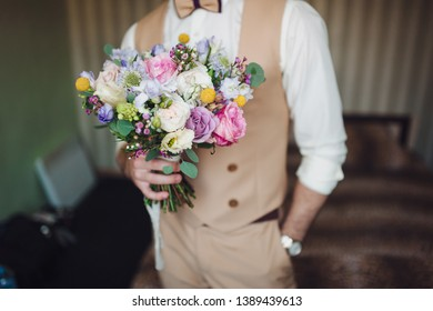 The groom in a beige suit and waistcoat holds a beautiful wedding bouquet of roses. Waiting for the bride. Morning groom. Wedding details. Composition and concept.