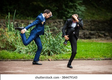 Groom and bestman dancing and goofing around after wedding ceremony in the park