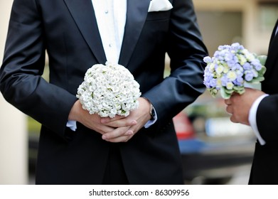 Groom and a bestman holding flowers during the wedding ceremony