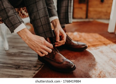 Groom in black grey checkered wedding suit, white shirt, sitting on the chair and tied shoelaces on brown leather shoes. Business clothing, men's style.