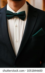 Groom black suit with a green bow tie