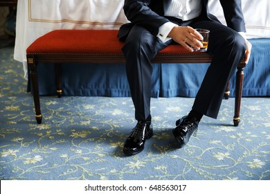 The groom in a black suit sits on a chair with a glass of whiskey.