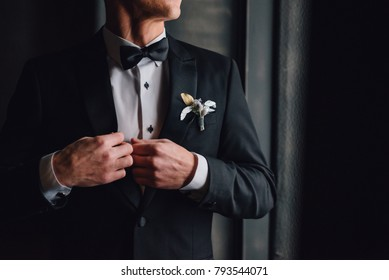 Groom in black tuxedo and bowtie correct his buttons on white shirt. Wedding. Details