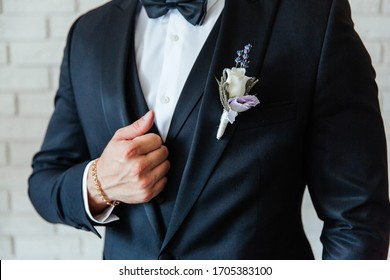 the groom in a black wedding suit, a tuxedo in a white shirt and a buttonhole