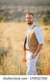 The groom in a blue shirt and brown vest waiting for the bride in a field on the hill. Wedding in rustic style. A man's portrait