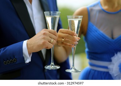 The groom in a blue suit and the bride in a blue dress standing with glasses in which is poured the champagne