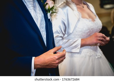 Groom in blue suit holding the wedding ring before he put to bride finger in the church during wedding ceremony. Matt film effect