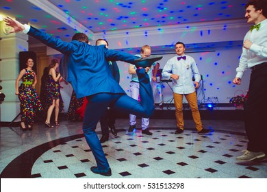 Groom in blue suit holds his leg while jumping on the dancefloor