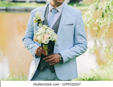 Groom in blue suit is standing outdoors. Handsome man is holding the wedding bouquet.