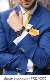 The groom in blue suit, watch and boutonniere.