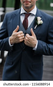 Groom in blue tuxedo and bowtie hold his hands on jacket. Wedding. Details