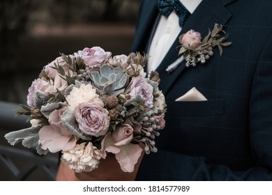 Groom in blue tuxedo holding wedding bouquet close up shot. Flower boutonniere decoration on husband tuxedo close up. Wedding clothing concept.
