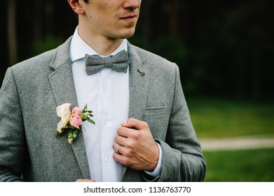 The groom with boutonniere or buttonhole on the jacket, bow tie, is stands on the background greenery in the garden.