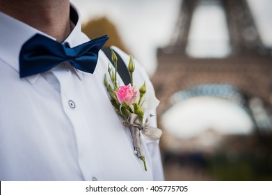Groom with boutonniere standing under the Eiffel Tower in Paris, France