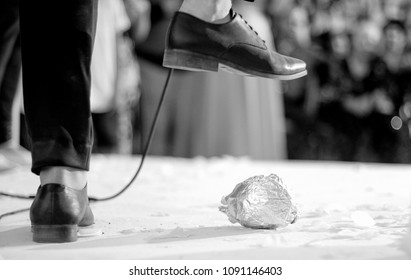 Groom breaking a glass at a Jewish wedding ceremony (black and white)