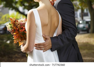 groom and bride with autumn bouquet outdoors. closeup of a married couple. Goose bumps and shivers at the bride. the bride wearing a wedding dress with a deep neckline at the back