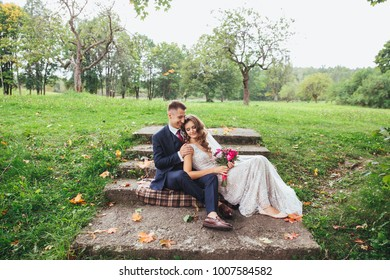 Groom bride with a bouquet hugging and sitting in park