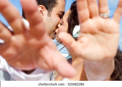 groom and bride cover camera with their hands while kissing