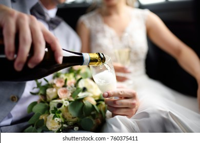 Groom and bride drinking sparkling wine (champagne) during celebration their wedding day. Happy wedding day